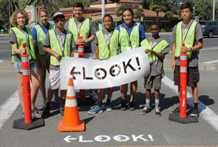 """A group of people in traffic vests hold a sign that reads """"Look"""""""