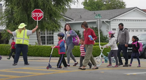 Adults and children crossing an intersection on a crosswalk.