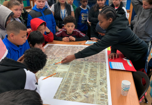 Students stand around a table with a large map on it. One student is pointing to a location on the map with a pencil.